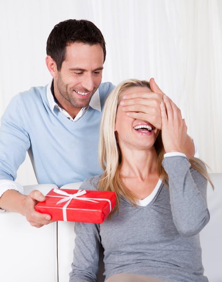 Человек давая его супруге подарок сярприза стоковая фотография rf