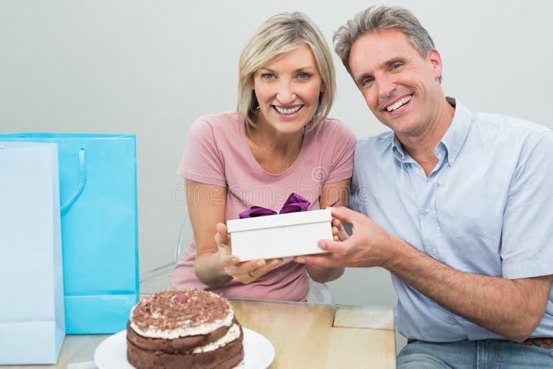 Укомплектуйте личным составом давать счастливой женщине подарок на день рождения около торта стоковое фото
