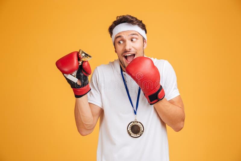 Укомплектуйте личным составом боксера в красных перчатках с чашкой и медалью трофея стоковое изображение rf