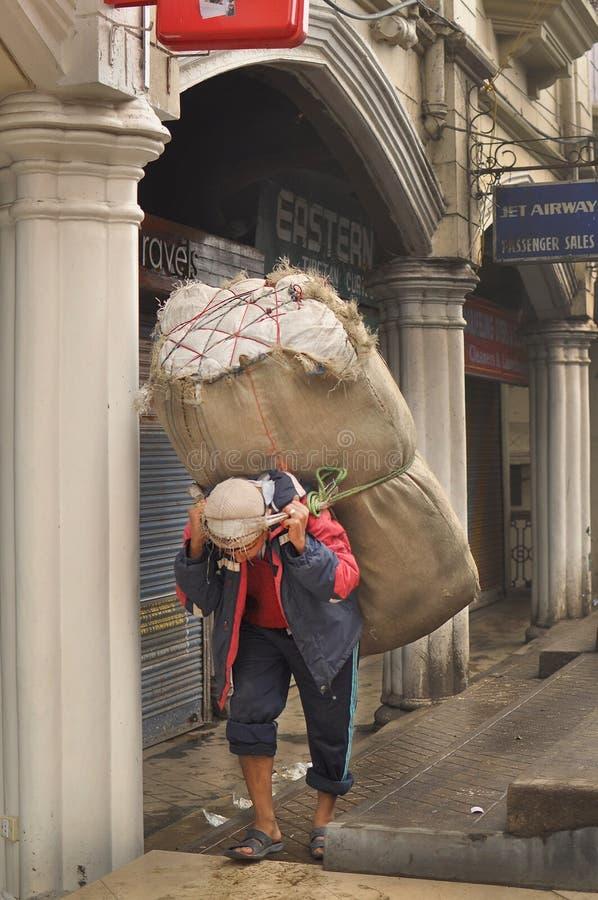 Укомплектуйте личным составом большой мешок нося на улице, взгляде утра Darjeeling, Индии 12-ого апреля 2012 стоковое изображение