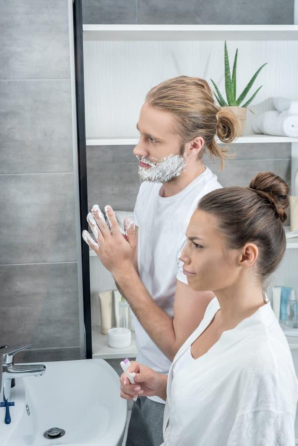 Укомплектуйте личным составом брить его бороду пока зубы женщины чистя щеткой в ванной комнате стоковое фото