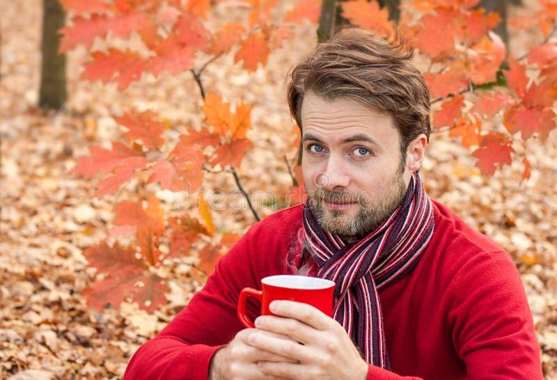 Укомплектуйте личным составом выпивая горячий чай внешний в парке пока пикник осени стоковая фотография rf