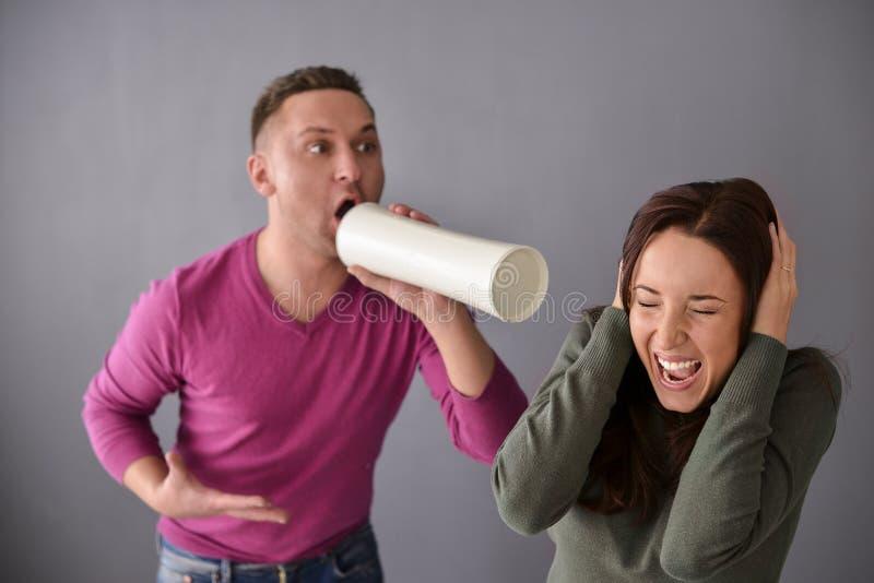 Укомплектуйте личным составом говорить через трубку и женщину затыкая ее уши стоковая фотография rf