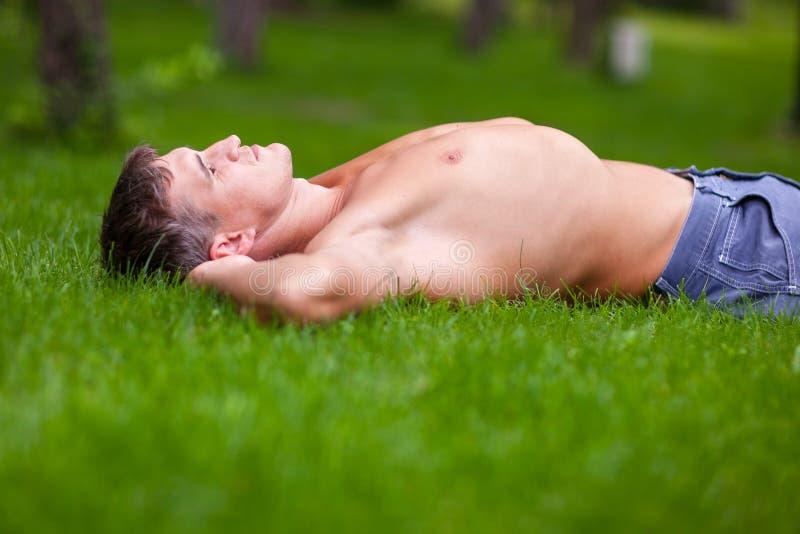 Укомплектуйте личным составом лежать на его задней части на траве стоковая фотография rf