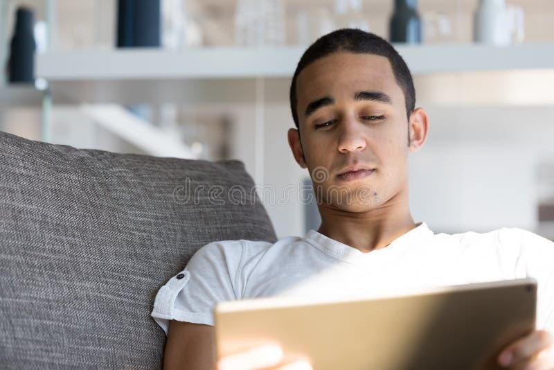 Укомплектуйте личным составом лежать на софе и смотреть таблетку стоковые фото