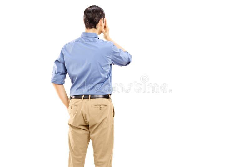 Укомплектуйте личным составом держать его руку против его глаза, вид сзади стоковые фото