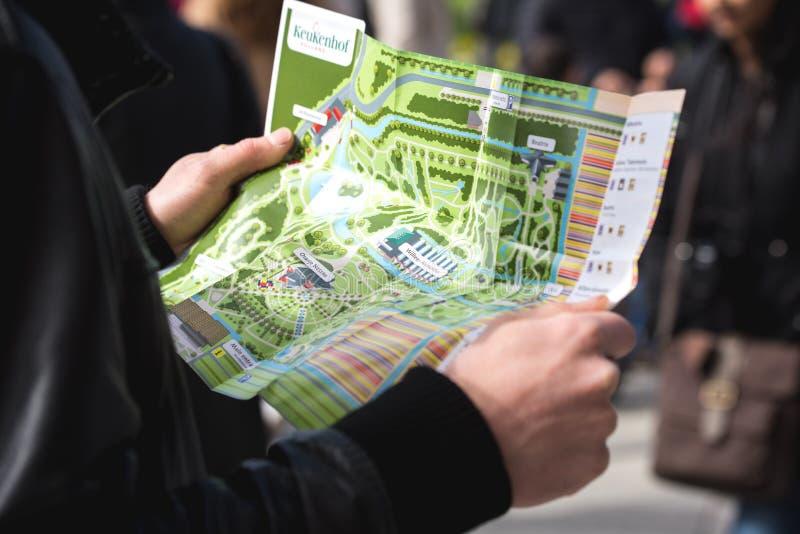 Укомплектуйте личным составом держать карту фестиваля цветка в Keukenhof стоковые изображения rf