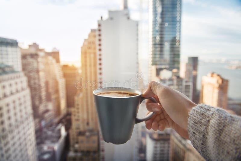 Укомплектуйте личным составом держать кофейную чашку в роскошных квартирах пентхауса с взглядом к Нью-Йорку стоковые изображения