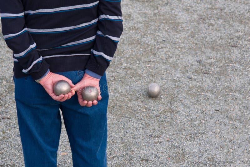 Укомплектуйте личным составом держать 2 шарика за его задней играя игрой в петанки стоковые изображения rf