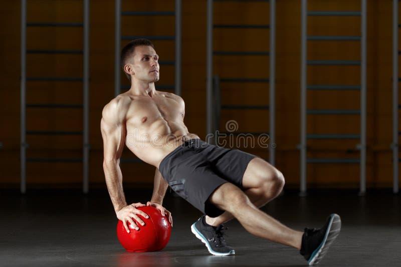 Укомплектуйте личным составом делать тренировку для мышц задней части с шариком фитнеса стоковые изображения rf