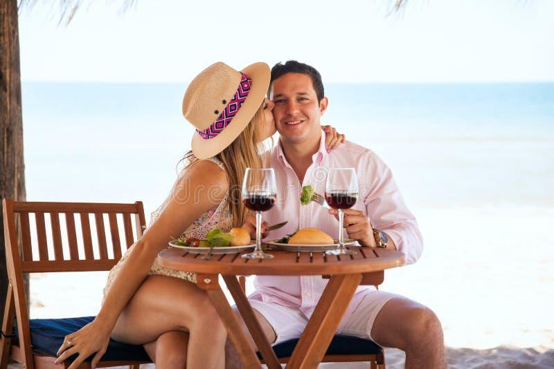 Укомплектуйте личным составом еду с его подругой на пляже стоковые фотографии rf