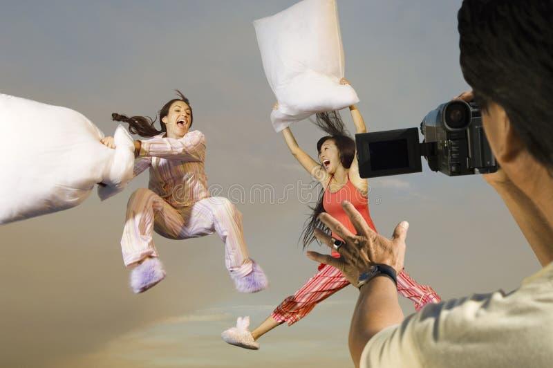 Укомплектуйте личным составом женщин видеозаписи 2 шаловливых в sleepwear имея бой подушками стоковые фото