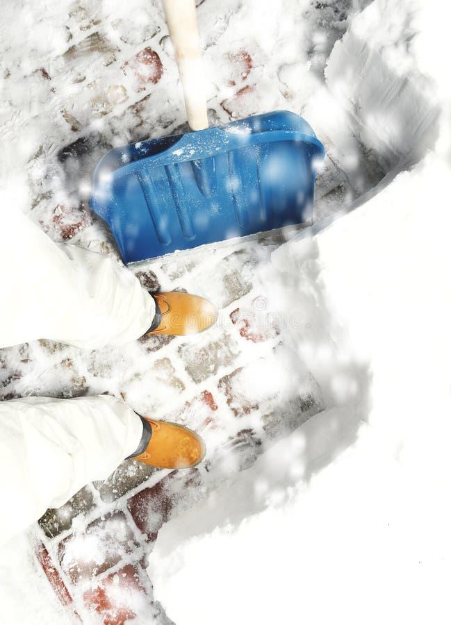 Укомплектуйте личным составом извлекать снег на задворк с лопаткоулавливателем во время снежностей стоковая фотография
