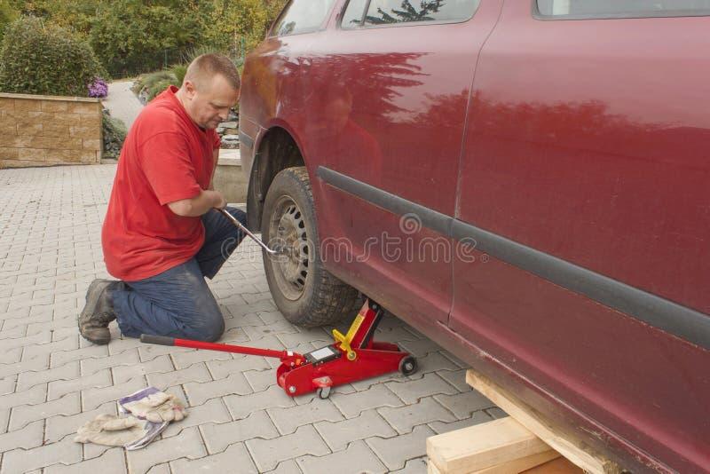 Укомплектуйте личным составом изменять прокалыванную покрышку на его автомобиле отпуская гайки с гаечным ключом колеса перед подн стоковые изображения