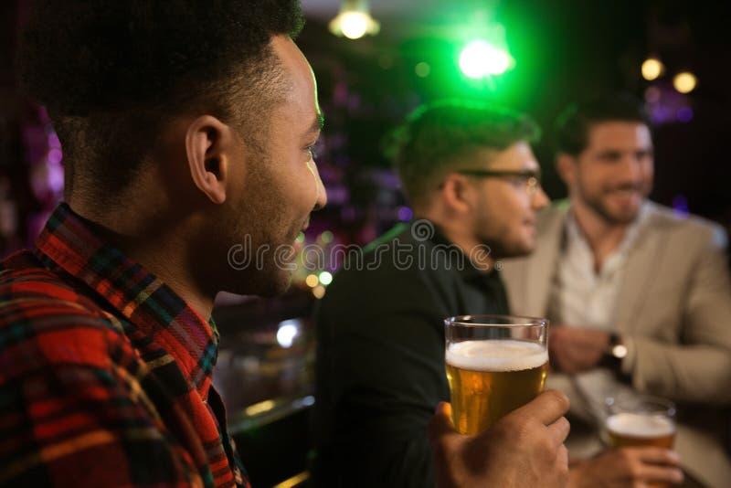 Укомплектуйте личным составом иметь пиво с его друзьями в пабе стоковые фото