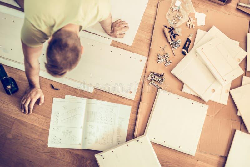 Укомплектуйте личным составом инструкции по монтажу мебели и клал сторону пола, взгляд сверху стоковые фото