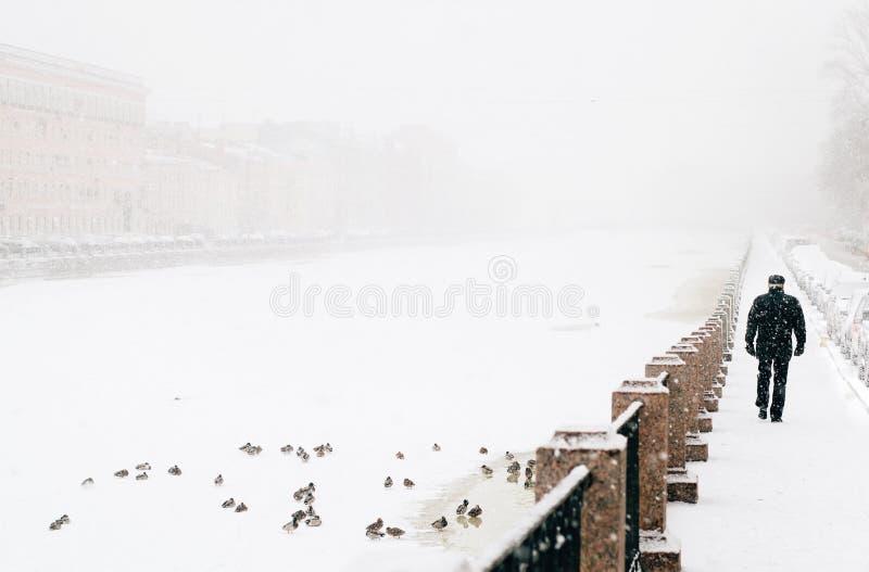 Укомплектуйте личным составом идти вдоль берега в тумане стоковые изображения