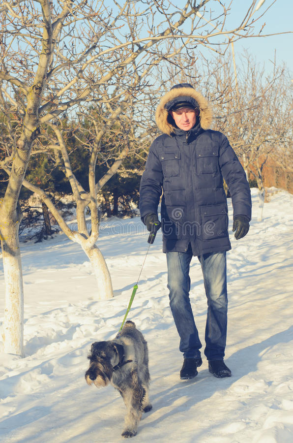 Укомплектуйте личным составом идти его собака на снежном пути стоковая фотография rf
