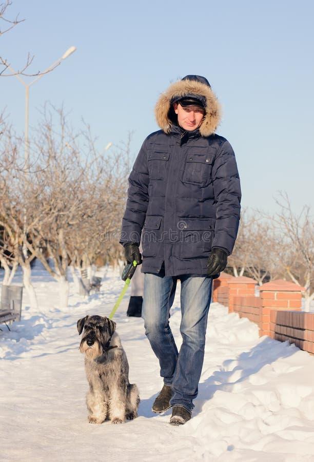 Укомплектуйте личным составом идти его собака на снежном пути стоковое фото
