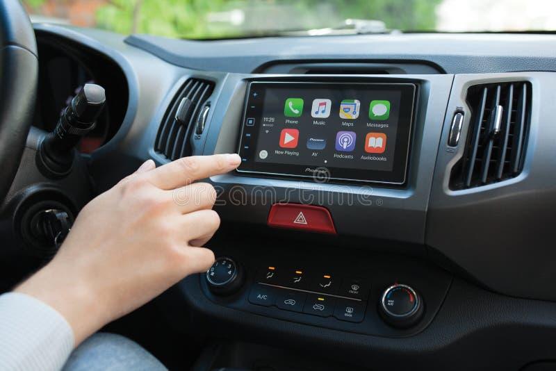 Укомплектуйте личным составом касаться к мультимедийной системе главного экрана с игрой автомобиля стоковое фото rf
