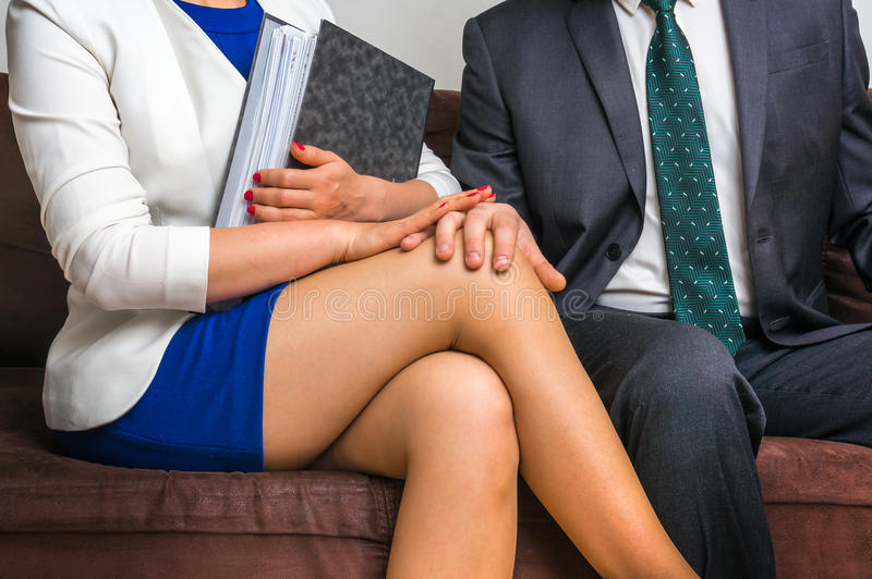 Укомплектуйте личным составом касающее колено ` s женщины - сексуальные домогательства в офисе стоковые изображения rf