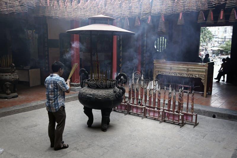 Укомплектуйте личным составом молить в виске ладана заполненном дымом в Хошимине стоковые изображения rf