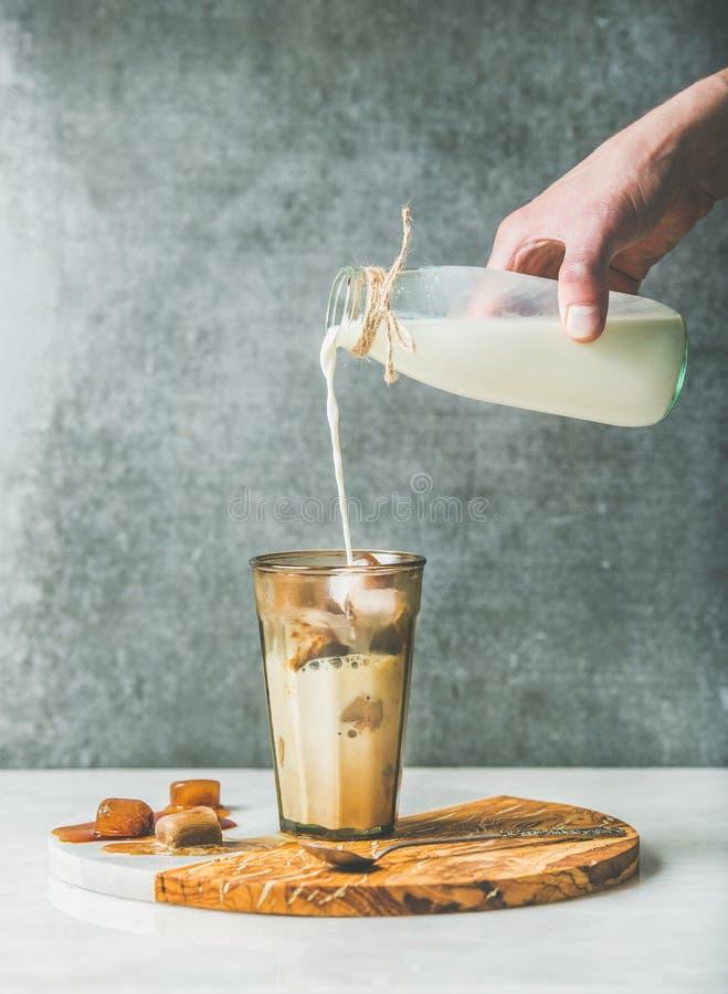 Укомплектуйте личным составом молоко руки ` s лить к замороженному коктеилю кофе карамельки latte стоковое фото rf