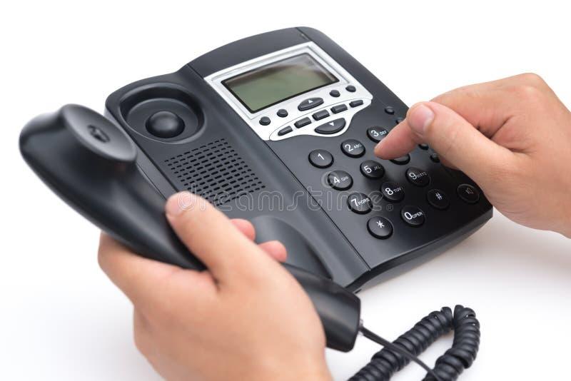 Укомплектуйте личным составом набирать черный телефон на белой предпосылке стоковые изображения