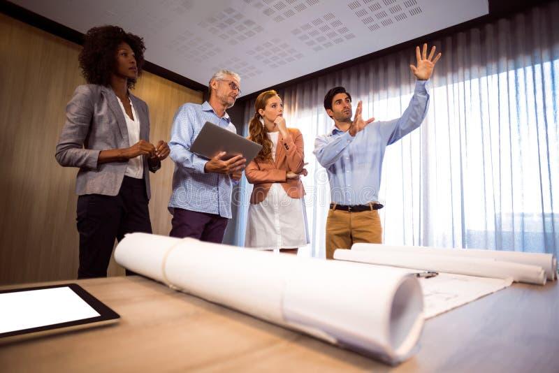 Укомплектуйте личным составом обрамлять с рукой пока стоящ в комнате правления с коллегами стоковая фотография