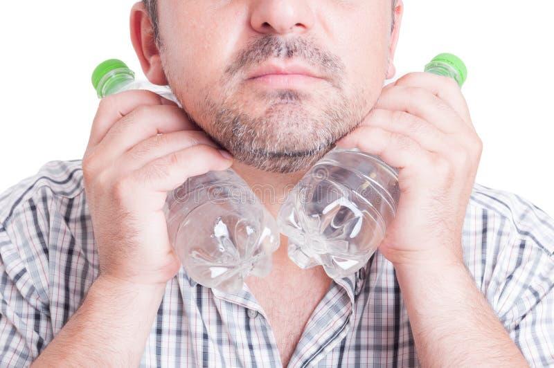 Укомплектуйте личным составом охлаждать его шею используя бутылки пластмассы холодной воды стоковые фото