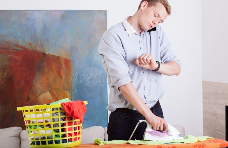 Укомплектуйте личным составом одежды и взгляды утюгов на его вахта стоковое изображение rf