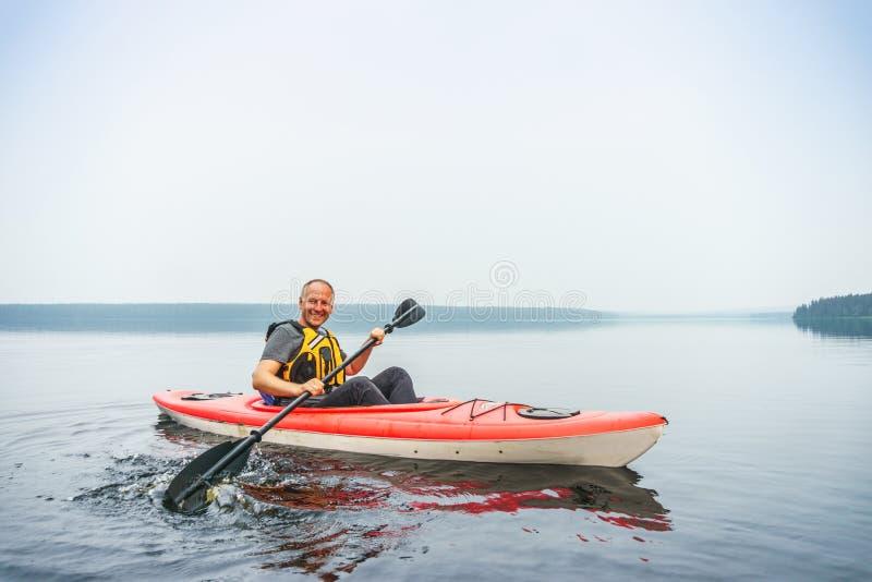 Укомплектуйте личным составом полоскать в каяке на затишье, туманном озере стоковые фото