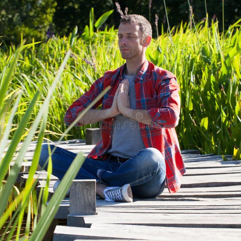 Укомплектуйте личным составом практикуя йогу сидя на деревянном мосте с тростником вокруг стоковое фото