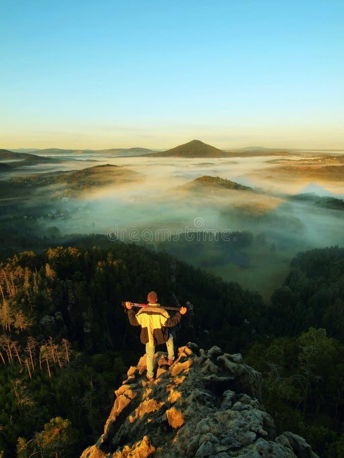 Укомплектуйте личным составом пребывание на скалистом пике и внутри вахта рассвета над туманной и туманной долиной утра утро осен стоковые изображения rf