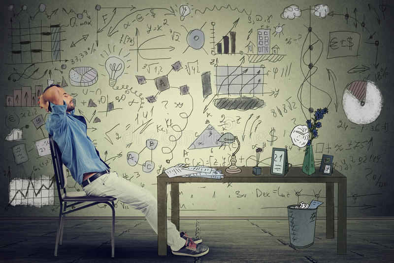Укомплектуйте личным составом предпринимателя ослабляя на его столе в его офисе стоковое фото