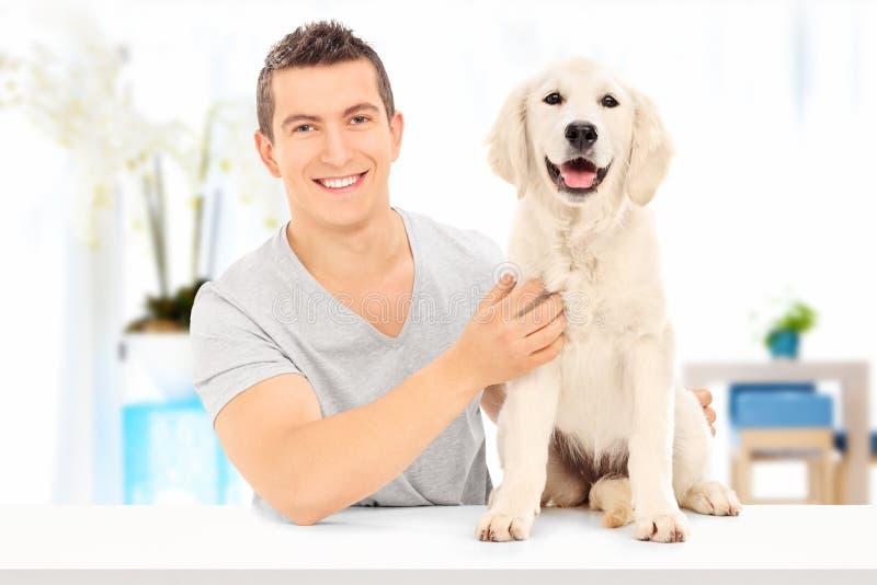 Укомплектуйте личным составом представлять при его собака усаженная на таблицу внутри помещения стоковые изображения
