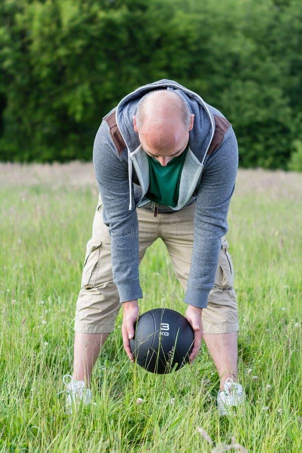 Укомплектуйте личным составом работать с 3 кило шарика медицины outdoors стоковые изображения
