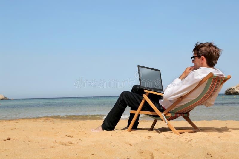 Укомплектуйте личным составом работу на его ПК на пляже стоковые изображения rf