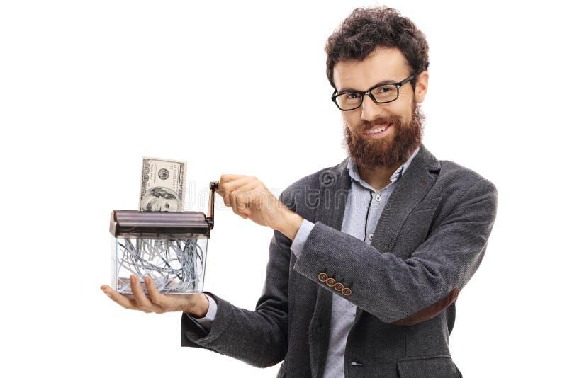 Укомплектуйте личным составом разрушать банкноту доллара в бумажном шредере стоковое фото rf
