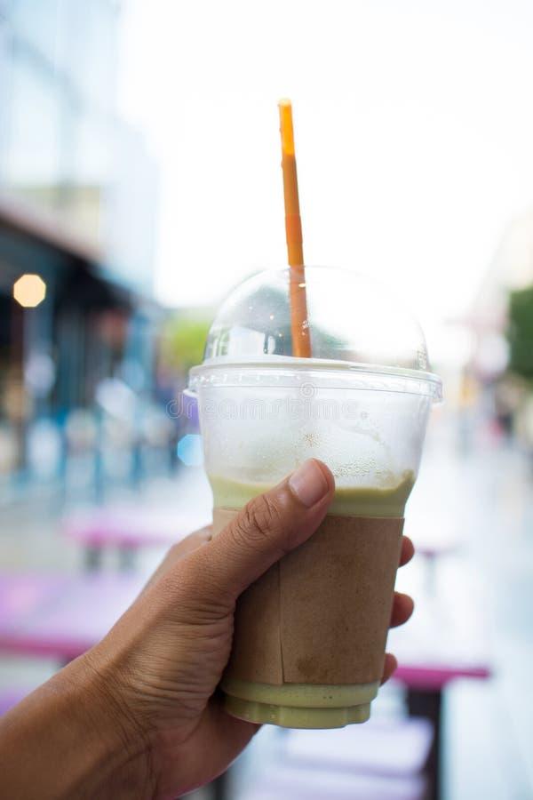 Укомплектуйте личным составом руку держа пластичное стекло замороженного чая молока зеленого стоковая фотография rf
