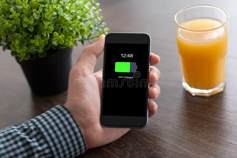 Укомплектуйте личным составом руку держа телефон с порученным экраном батареи в офисе стоковое фото