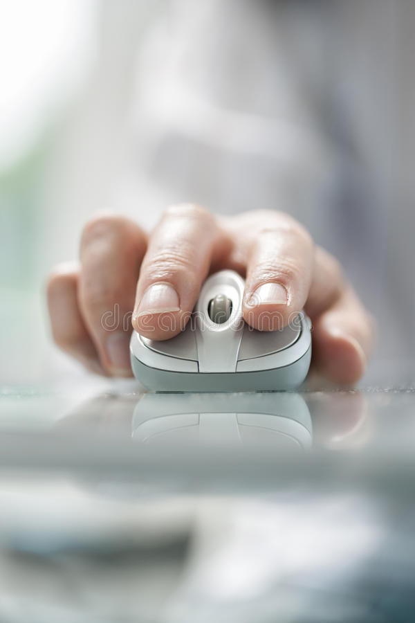 Укомплектуйте личным составом руку ` s используя бесшнуровую мышь на стеклянном столе стоковые изображения