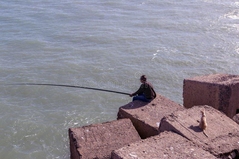 Укомплектуйте личным составом рыбную ловлю от утесов на краю банка моря, watche кота стоковые фото