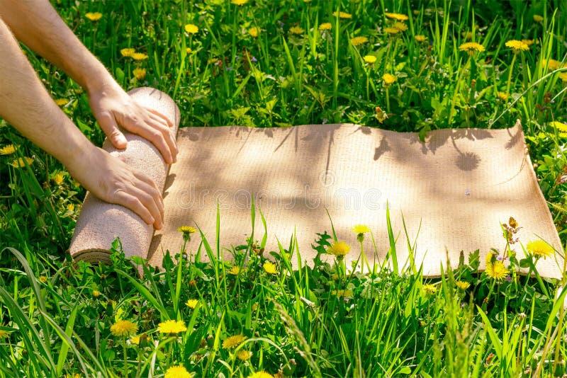 Укомплектуйте личным составом свертывать ее циновку после занятий йогой на зеленом луге на день лета солнечный стоковое фото rf