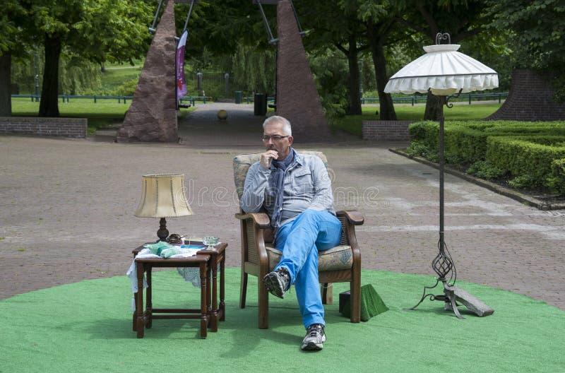 Укомплектуйте личным составом сидеть в парке на стуле с таблицей и лампой стоковое изображение rf