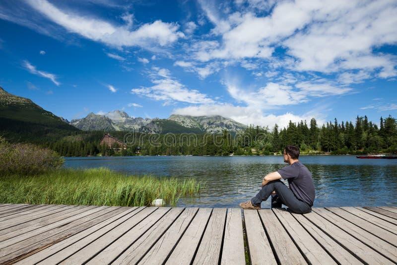 Укомплектуйте личным составом сидеть на банке озера горы стоковые изображения rf