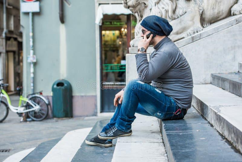 Укомплектуйте личным составом сидеть на лестницах и говорить на телефоне стоковое изображение