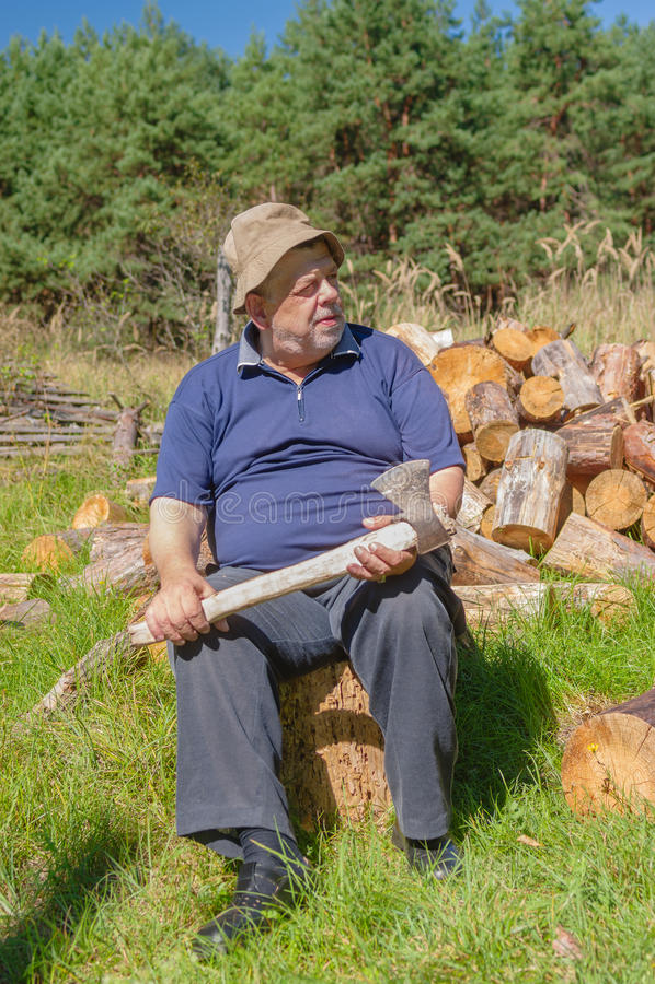 Укомплектуйте личным составом сидеть на журнале получая готовый прервать кучу firewoods для разжигать зимы стоковая фотография