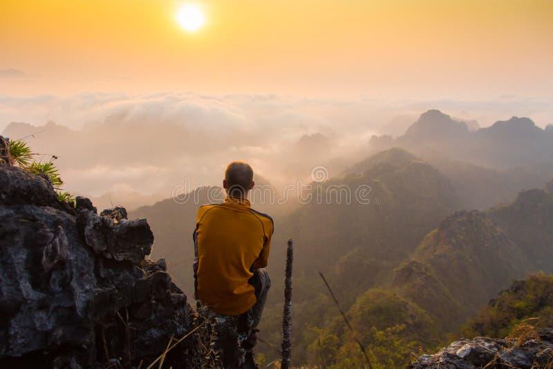 Укомплектуйте личным составом сидеть на каменной верхней части высокой горы стоковое фото