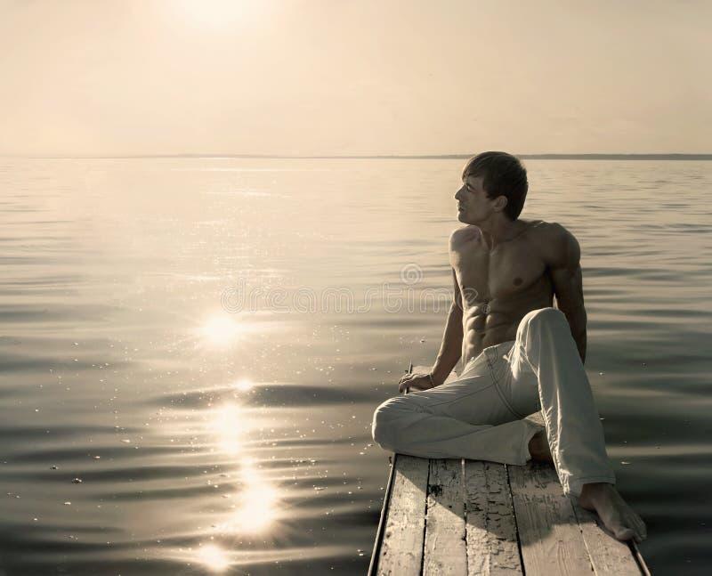 Укомплектуйте личным составом сидеть на малой деревянной моле на дне лета солнечном стоковая фотография